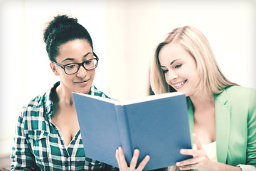 smiling student girls reading book at school