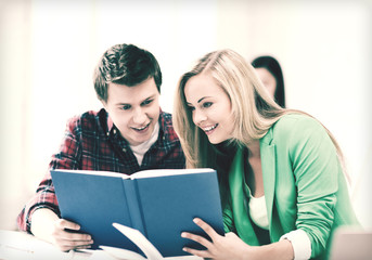 girl and guy reading book at school