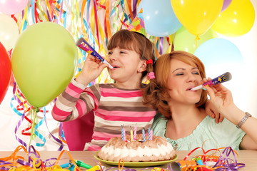 happy daughter and mother with trumpets and balloons on birthday
