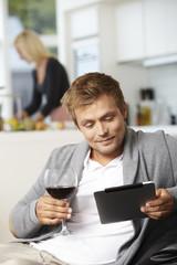 Mid adult man using digital tablet at home