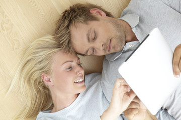 Mid adult couple lying on floor using tablet