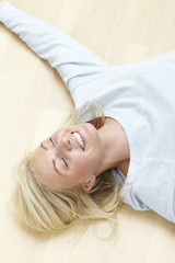 Mid adult woman relaxing on floor, smiling