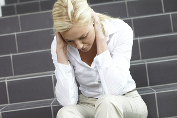Distraught blonde woman on staircase