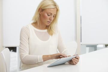 Mid adult woman using digital tablet