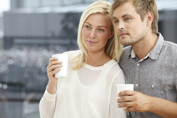Mid adult couple holding takeaway coffee cups