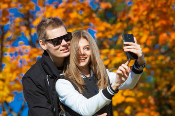 man with girl in an autumn park. Two being photographed yourself