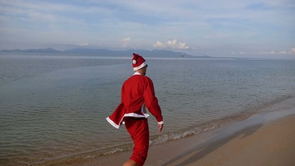 Happy Santa Claus Walking at Tropical Sunny Beach.