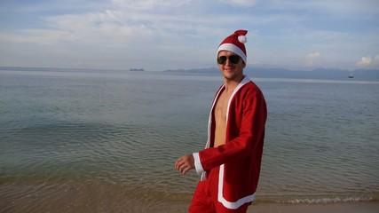 Santa Claus Happy Jumping at Beach. Holiday Vacation.