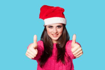 Brunette girl in christmas hat on blue background.
