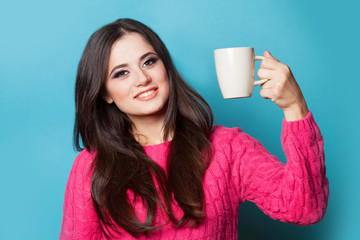 Brunette girl with cup on blue background.