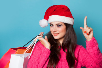 Brunette girl in christmas hat with shopping bags on blue backgr