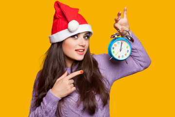 Brunette girl with alarm clock on yellow background.