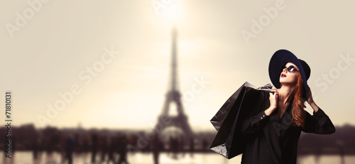 Redhead women with shopping bags on parisian background. - 71810131
