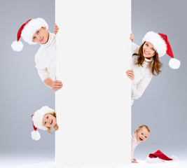Christmas family in Santa's hats with banner