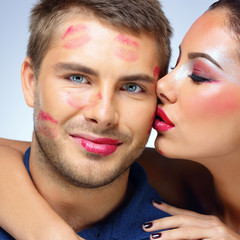 Attractive woman kissing happy man over blue background