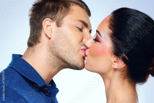 canvas print picture Young couple of lovers kissing isolated on blue background