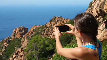 Young woman uses a smartphone to video a beautiful view