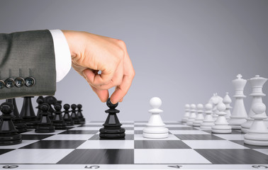 Businessman hand touching pawn figure on chess board