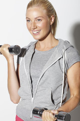Mid adult woman in sportswear lifting weights, smiling