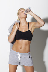 Mid adult woman in sportswear drinking water