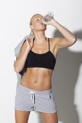 Mid adult woman in sportswear drinking water