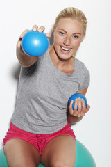 Mid adult woman exercising on Swiss ball, portrait
