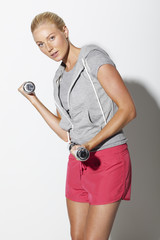 Mid adult woman in sportswear lifting weights, portrait