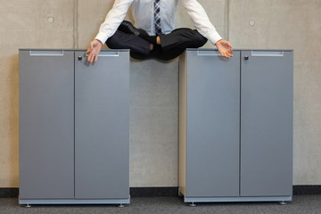 meditating businessman  in lotus pose  on cabinets in office