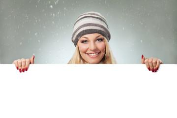 Blond woman holding blank banner. Winter theme. Studio shot.