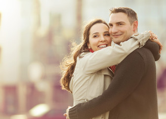 Young couple embracing in the sity street and looking happy.