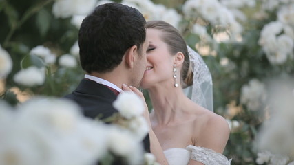 Newlyweds touchingly kissing while standing among white blooming