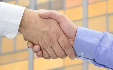 Hände beim Vertragsabschluss vor Orange