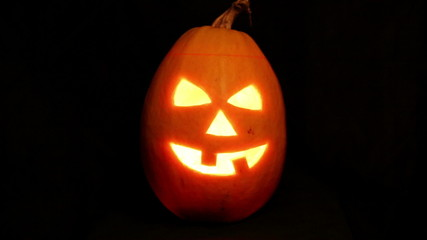 Halloween pumpkin jack-o-lantern candle lit, isolated on black