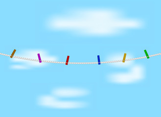 Coloured clothespins on white rope and blue sky