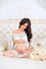Beautiful pregnant brunette sitting on a bed