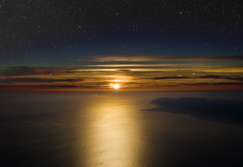 High altitude sunset. Stars above, cloudsand sea below.