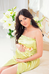 Pregnant in  tender light green dress on a sofa with lilies