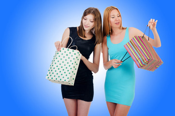 Girls with shopping bags on white