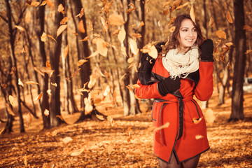 smiling brunet in red coat in falling autumn leafs