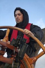 Young sailor steering tall ship