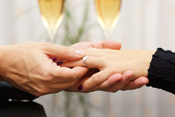 Man putting  engagement ring on the finger of his fiance