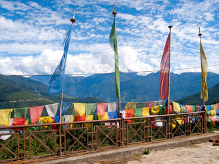Colorful prayer flags over a blue sky at a temple in Bhutan