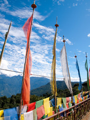 Colorful prayer flags over a blue sky near a temple in Bhutan
