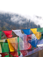 Colorful prayer flags over the misty himalayas in Bhutan