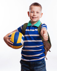 Happy schoolboy with backpack and soccer ball