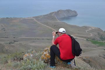 Турист на горе, вид на море