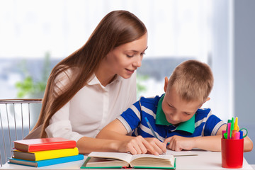Mother Helping Son With Homework At Table