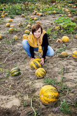 Young caucasian woman working on the pumpkin field