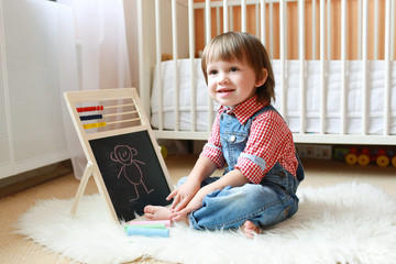 2 years toddler draws on the blackboard with chalk