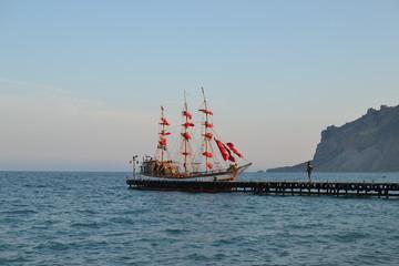 Яхта с алыми парусами на причале на море